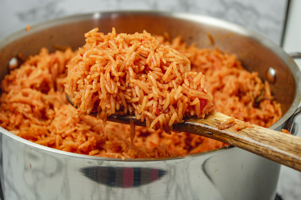 cooked rice on a ladle over a pot.