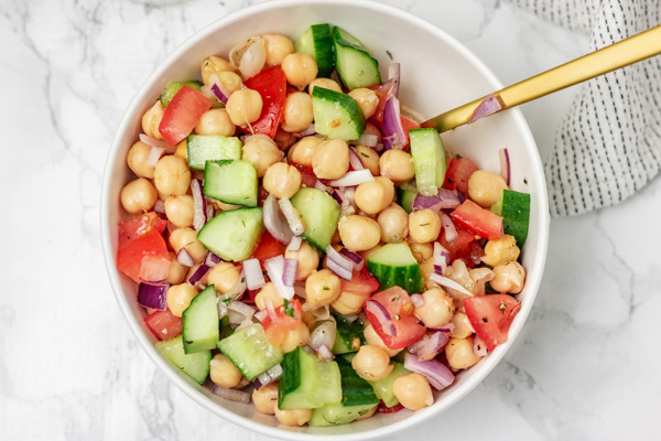a bowl of chickpea salad with golden serving spoon.