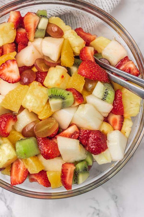 a bowl of fruit with spoon.