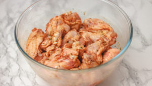seasoned uncooked chicken wings in a glass bowl.