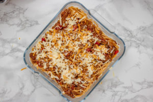 spaghetti and cheese in a baking dish.