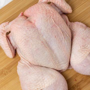 raw butterflied chicken on a chopping board.