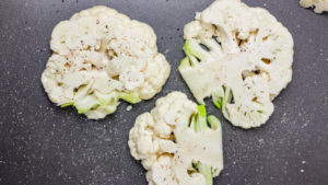 three cauliflower steaks in a baking tray