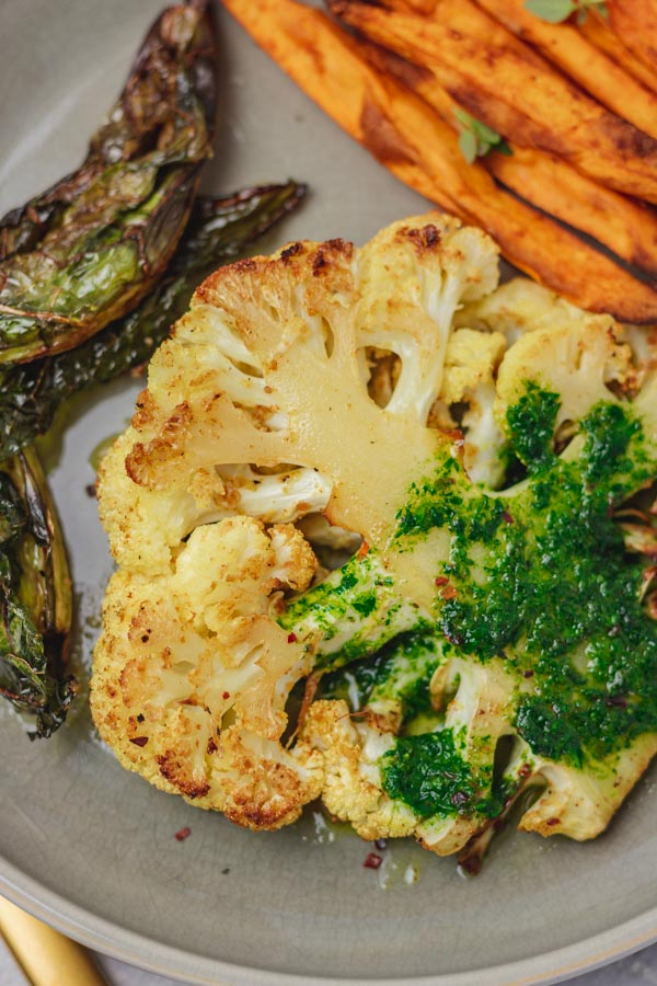 cauliflower steak covered with green sauce on a plate with sweet potato fries.