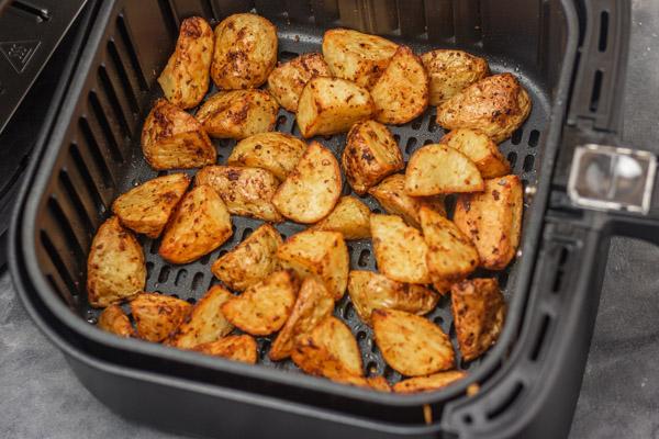 crispy diced potatoes in an air fryer basket.