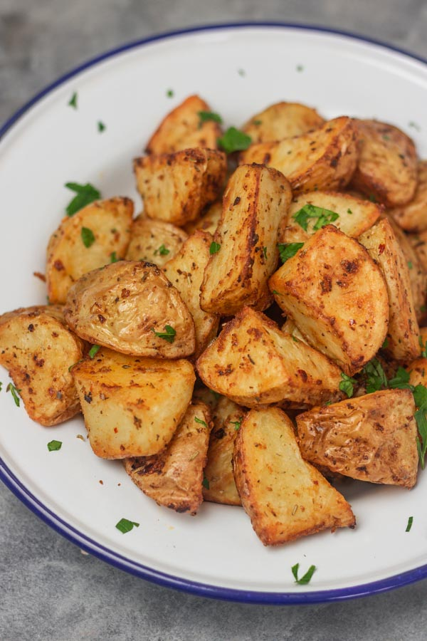 cubed roasted potatoes in an enamel white plate.