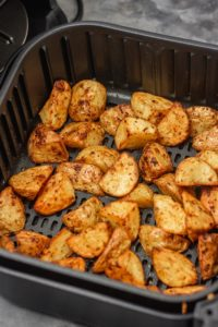 cubed roasted potatoes in air fryer basket.
