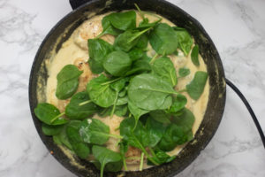 spinach and sauce in a pan.
