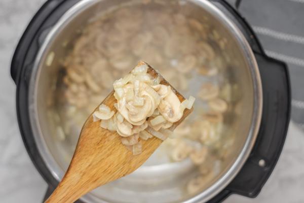 sauteed mushroom in a ladle.