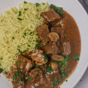 a plate of rice and beef with gravy.