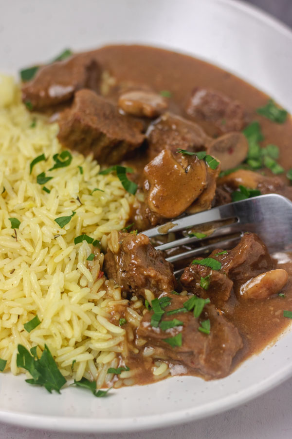 a plate of rice and beef with gravy garnished with chopped parsley.