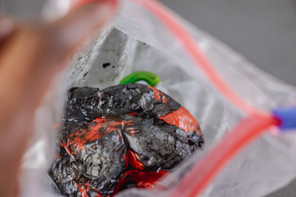 charred red bell pepper in a ziploc bag.