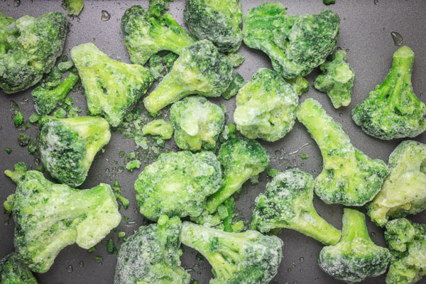 frozen broccoli florets on a tray.