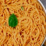 spaghetti garnished with basil in a skillet.