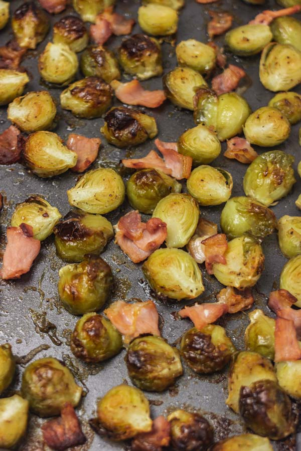 freshly roasted bacon and brussels sprouts in a baking tray.