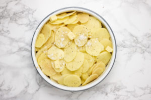 thinly sliced potatoes in a pie dish.