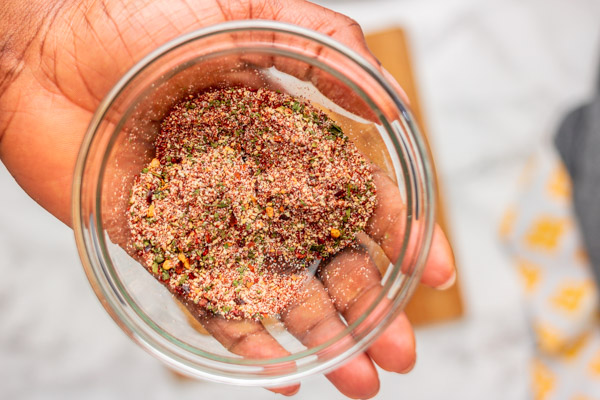 a hand holding a bowl of dry seasoning.