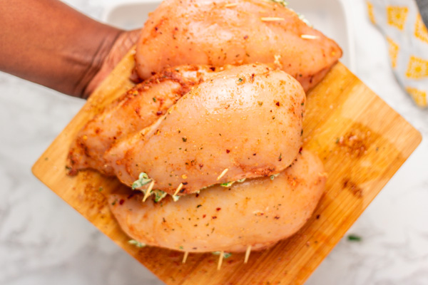 a hand holding a tray of uncooked chicken.