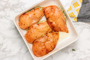 four stuffed chicken breasts in a baking dish.