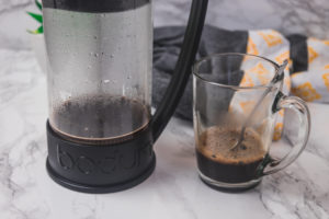 a glass of coffee and a french press