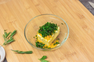 chopped herbs on a block of butter.