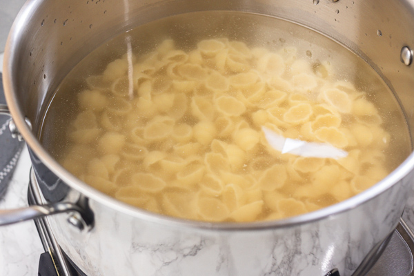 shell pasta cooking in a pot.