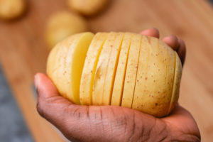 a hand holding an uncooked sliced potato.