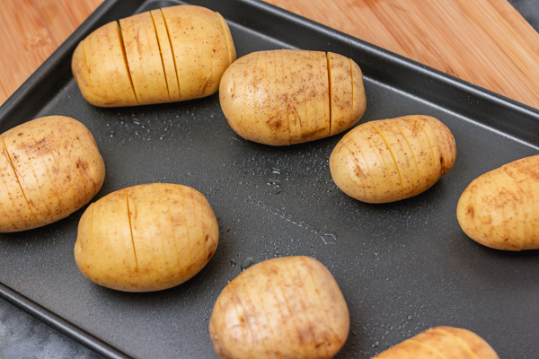 raw potatoes on a baking tray.