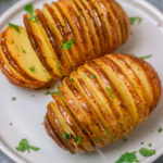 two hasselback potatoes on a side plate.