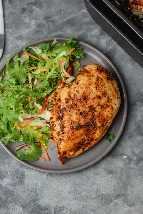 a plate of chicken and salad placed beside air fryer.