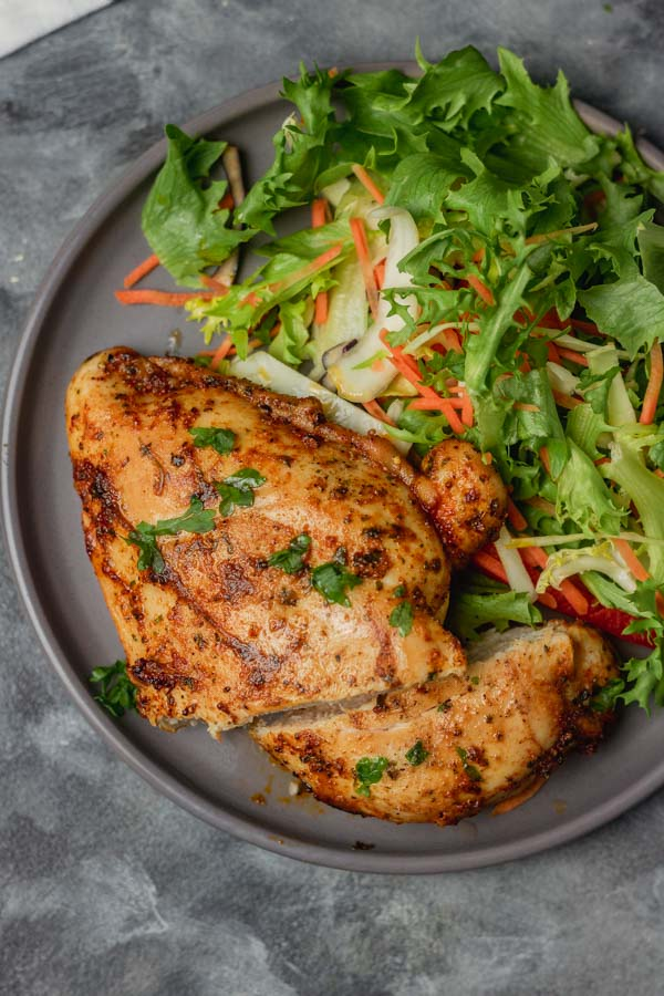 a plate of sliced chicken breast and salad.