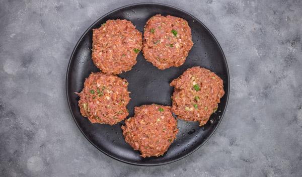 bfive patties on a black flat plate.