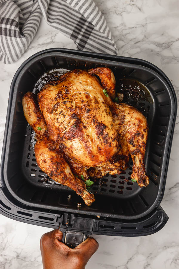 a hand holding a air fryer basket with chicken.