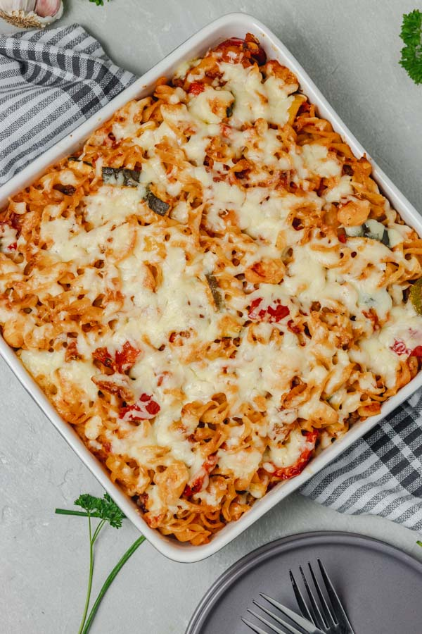 baked pasta in a baking dish placed on a white and gray napkin.