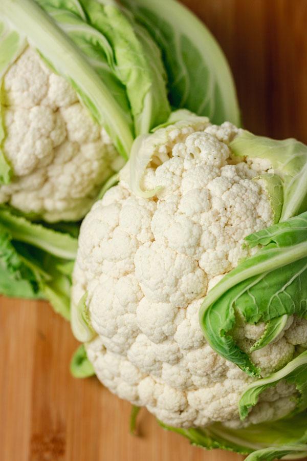 two cauliflower head on a chopping board.