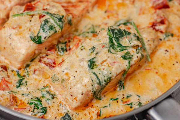 a close shot of fish covered in creamy sauce.