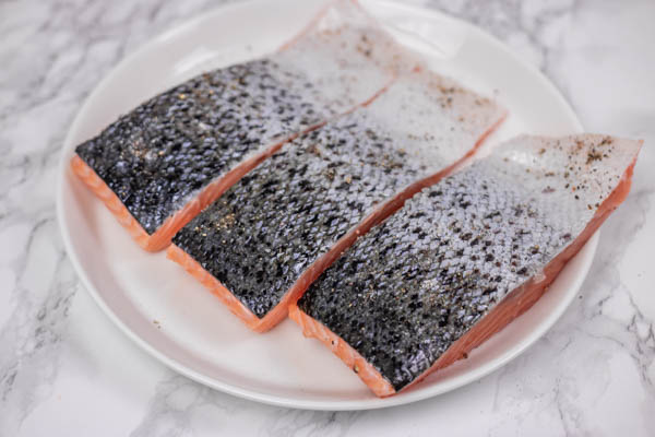 three raw salmon fillets on a plate.