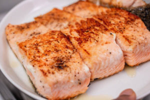 cooked salmon fillets on a plate.