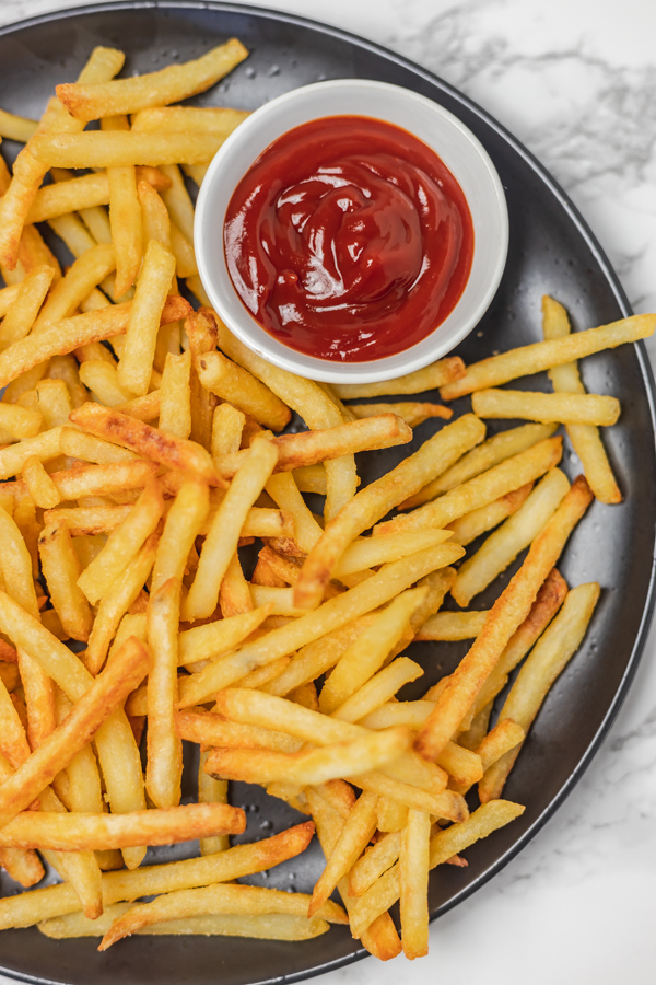 A plate of fries and ketchup.