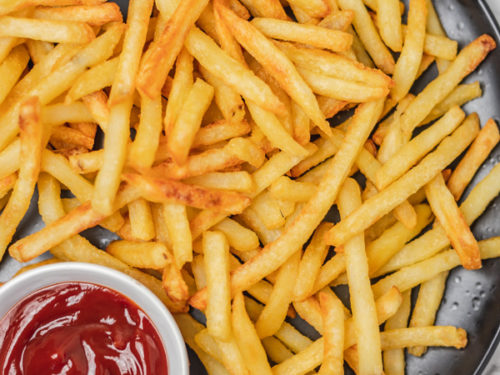 a plate of fries and a side of ketchup.