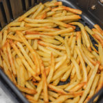 french fries in air fryer basket.