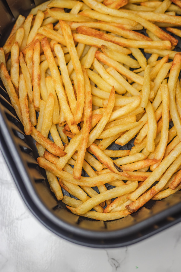 french fries in an air fryer basket.
