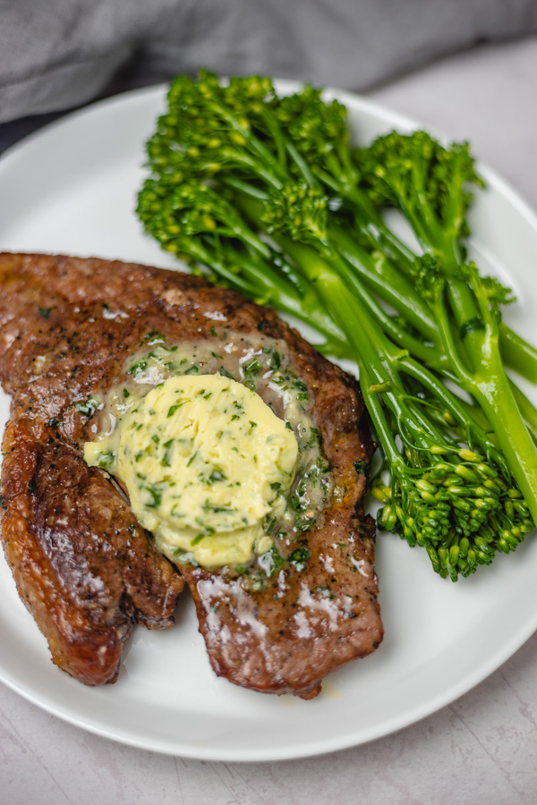 steak topped with herb butter with a side of broccoli stem.