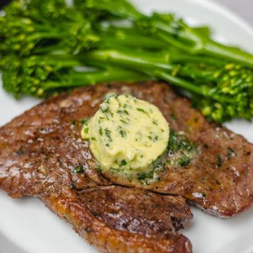 a plate of steak and broccoli stem.