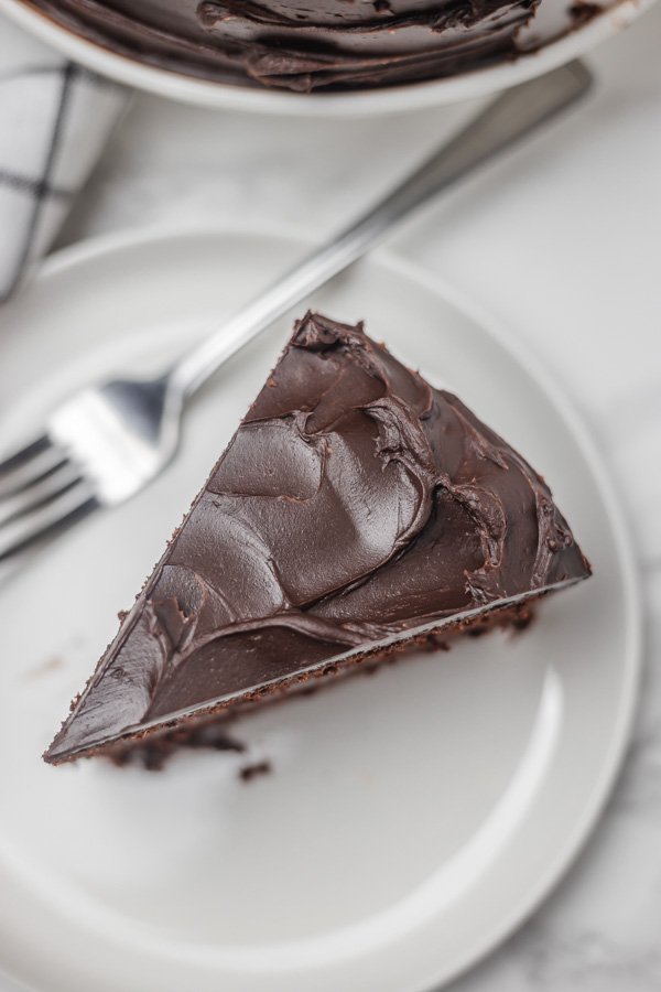 a slice of chocolate cake on a small white plate.