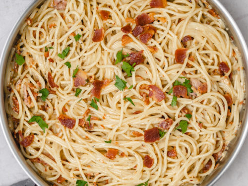pasta and bacon in a skillet.