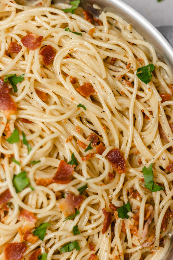 bacon crumbled over a pan of spaghetti.