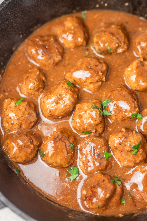 meatballs and gravy in a cast iron skillet.