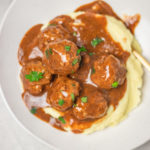 a white plate of meatballs and gravy served over mashed potato.