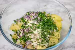 a mixing bowl of cubed potatoes covered with sauce and herbs.